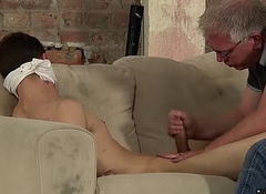 Romp twink slave on a dirty couch gets stroked by Sebastian